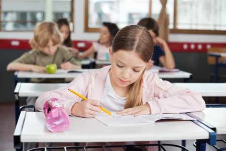 class room: Schoolgirl Drawing In Book At Classroom Stock Photo