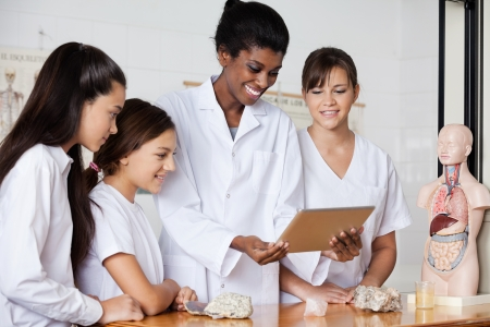 stone tablet: Teacher With Teenage Girls Using Digital Tablet At Desk Stock Photo
