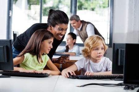 Female Teacher Assisting Schoolchildren In Using Computer