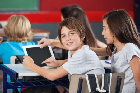 students in classroom: Boy With Girl Using Digital Tablet At Desk