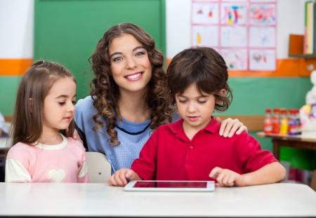 デスクでのデジタル タブレットを使用して子供たちと先生