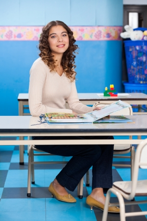 medium length: Teacher With Popup Book Sitting At Desk In Preschool Stock Photo