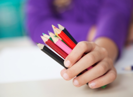 Girl Holding Colored Pencils At Desk photo