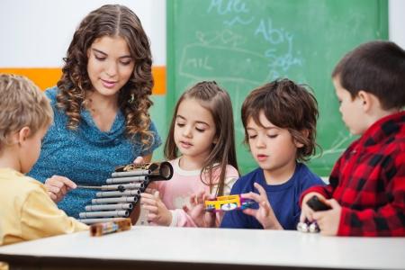 maestra ense�ando: Estudiantes de ense�anza del profesor Para tocar el xil�fono en clase