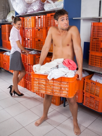 Man Holding Clothes basket With Businesswoman Looking At Him photo