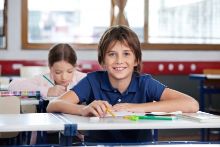 class room: Happy Little Boy Sitting At Desk