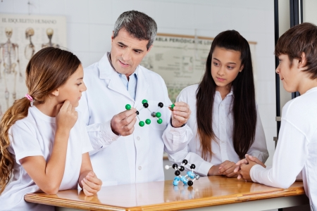 Teacher With Students Analyzing Molecular Atoms At Desk