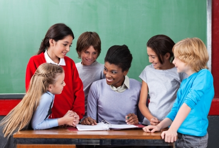 Happy Teacher Teaching Schoolchildren At Desk In Classroom Stock Photo - 20730631