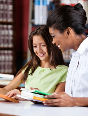 colegiala: Bibliotecario y colegiala mirando juntos Libro Foto de archivo