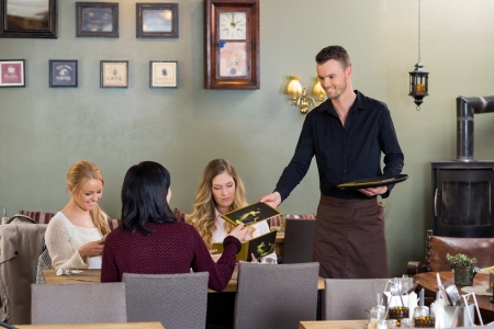 dining table and chairs: Young Waiter Giving Menu To Female Customers