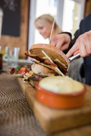 Man With Burger And Sauce On Wooden Plate Stock Photo - 20730647