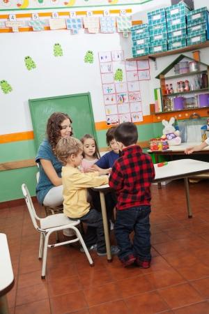 preschool education: Teacher Playing With Children In Kindergarten
