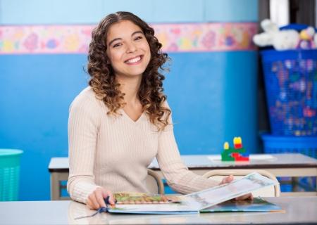 escuela primaria: Maestros con libro sentado en el escritorio