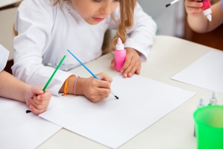 Girl Painting At Desk In Preschool Stock Photo - 20933167