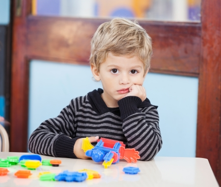Unhappy Boy With Blocks In Classroom photo