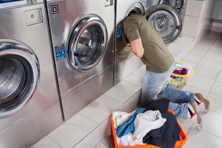 Man Searching Clothes Inside Washing Machine photo