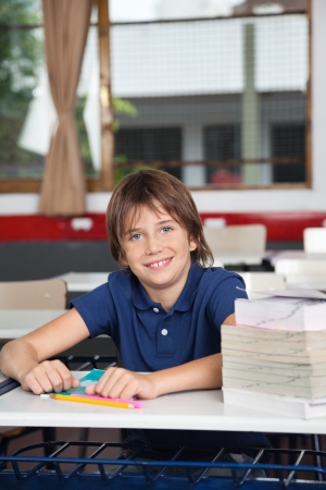 Schoolboy With Books And Globe At Desk photo