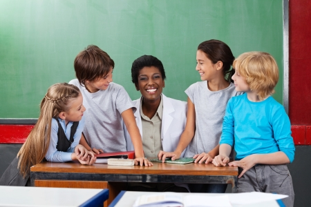 Teacher Sitting At Desk With Students At Desk Stock Photo - 20999158