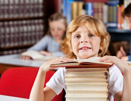 Schoolboy With Stack Of Books Sitting In Library photo
