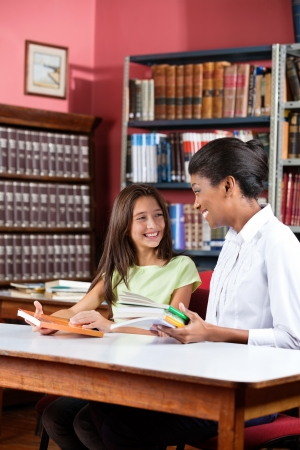 Librarian Teacher And Schoolgirl Looking At Each Other In Librar Stock Photo - 20999164