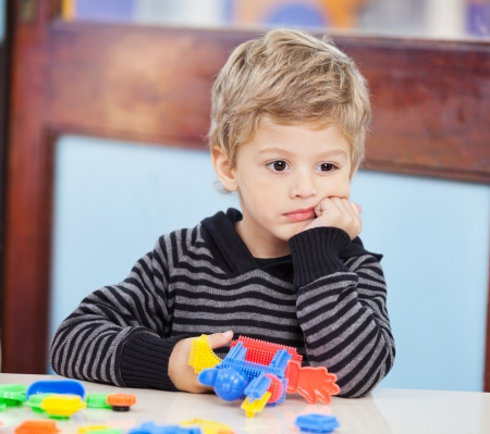 sad child: Boy With Blocks Looking Away In Preschool Stock Photo