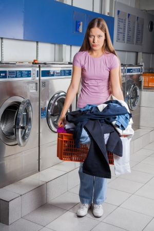 Upset Woman Holding Basket Full Of Dirty Clothes photo