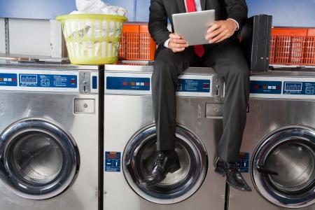 Businessman Using Digital Tablet While Sitting On Washing Machine photo