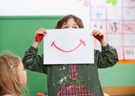 Boy Holding Drawing Paper On Face In Art Class Stock Photo - 21189015