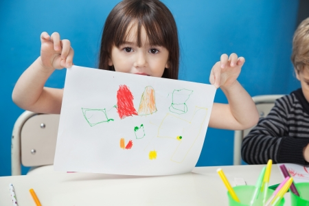 show case: Girl Holding Drawing Paper In Art Class Stock Photo