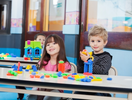 Little Children Playing With Blocks In Preschool photo