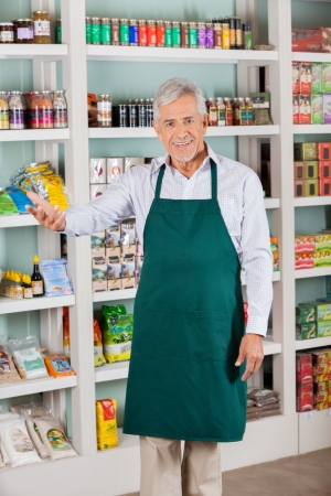 Male Store Owner Gesturing In Supermarket photo