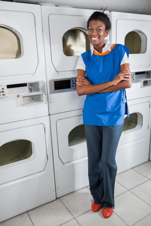 Confident Female Helper Standing By Dryers photo