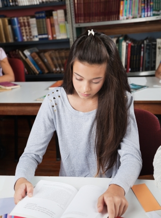 waistup: Female Student Reading Book At Table In Library Stock Photo