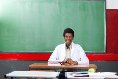 educators: Profesor joven sentado en el escritorio en el aula