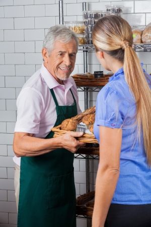 Male Owner Assisting Female Customer In Buying Muffins photo