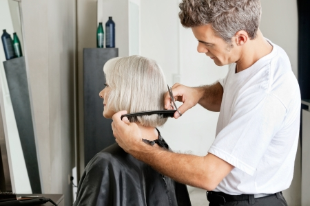 Hairdresser Examining Hair Length Of Client photo