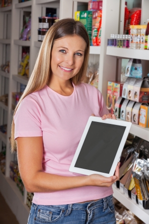 Portrait Of Woman Showing Digital Tablet At Grocery Store photo