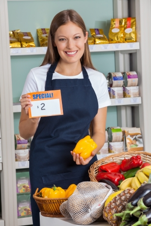 pricetag: Saleswoman Holding Pricetag And Bellpepper In Supermarket