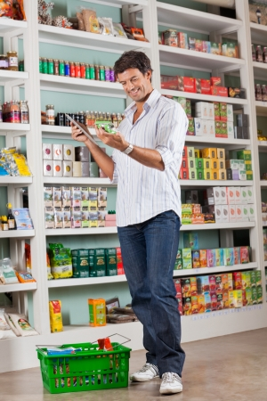 supermarket shelves: Man Checking Grocery List In Supermarket Stock Photo