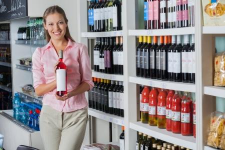 magasin: Jeune femme tenant une bouteille d'alcool