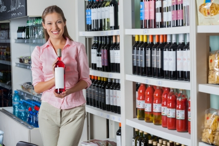 supermarket shelves: Young Woman Holding Bottle Of Alcohol Stock Photo
