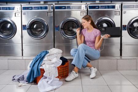 lavadora con ropa: Mujer que disfruta de música en lavandería