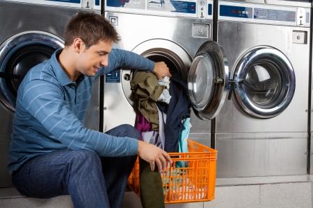 laundromat: Man Putting Clothes In Washing Machine Stock Photo