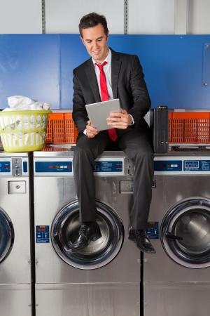 laundromat: Businessman Using Digital Tablet In Laundry