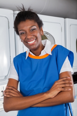 Female Helper Standing With Arms Crossed In Laundry photo
