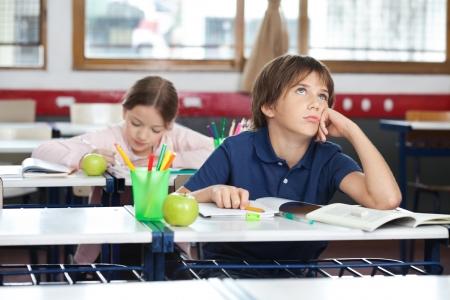 niños pensando: Muchacho joven que mira para arriba en sala de clase Foto de archivo