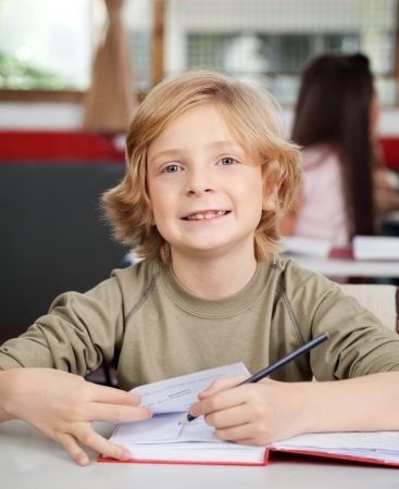 kids class: Portrait Of Schoolboy Writing In Book At Desk Stock Photo