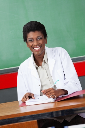 Happy Teacher With Pen And Binder Sitting At Desk Stock Photo - 21144582