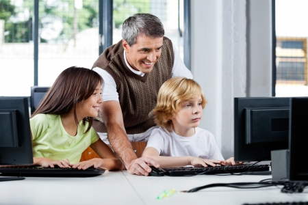 internet class: Happy Teacher Assisting Schoolchildren In Using Desktop Pc Stock Photo
