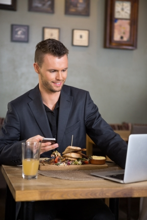 Businessman Using Laptop While Having Food In Restaurant Stock Photo - 21144587